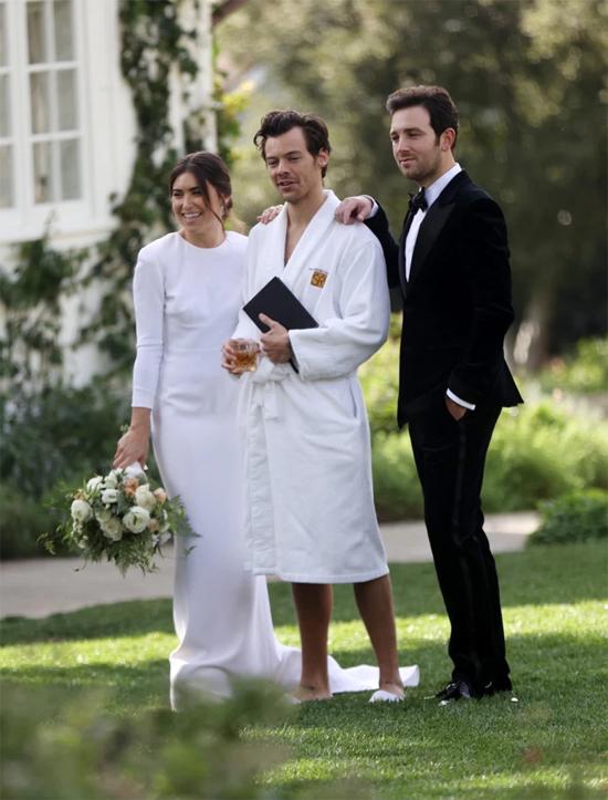 Harry chụp ảnh cùng cô dâu - chú rể trong đám cưới.