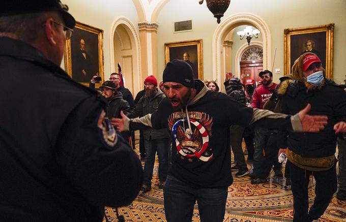 Những người biểu tình tỏ ra thách thức một cảnh sát ở hành lang bên ngoài phòng Thượng viện Đồi Capitol.