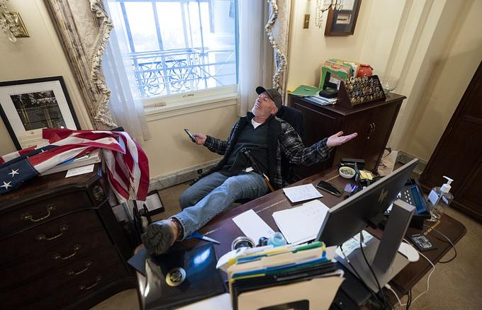 Một người đàn ông mặc quần jean và đội mũ lưỡi trai  gác chân lên bàn của Chủ tịch Hạ viện Nancy Pelosi.