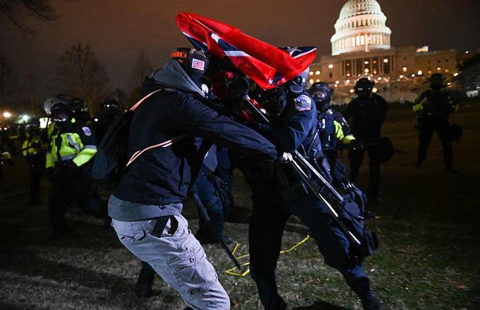 Một người biểu tình đối đầu với một nhân viên cảnh sát chống bạo động bên ngoài Đồi Capitol.