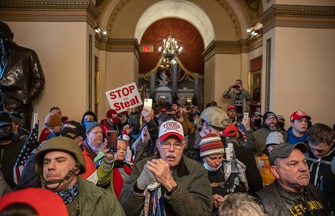 Người biểu tình không đeo khẩu trang, tràn vào bên trong sảnh Đồi Capitol. Họ đội mũ lưỡi trai ủng hộ ông Trump, giơ biển hiệu có dòng chữ Stop the Steal, nhằm phản đối gian lận bầu cử.