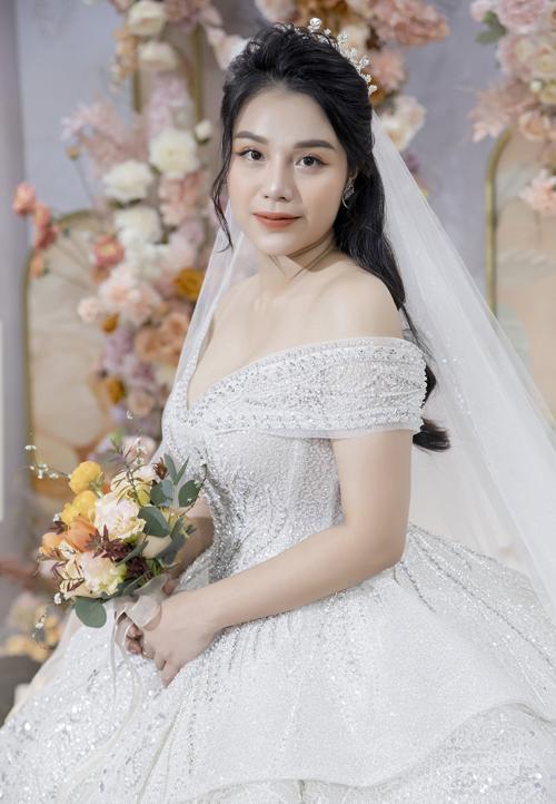 Bùi Tiến Dũng hiểu các ưu, khuyết điểm về vóc dáng cô dâu nên đã trao đổi với NTK để cho ra đời váy cưới trễ vai xòe phồng.