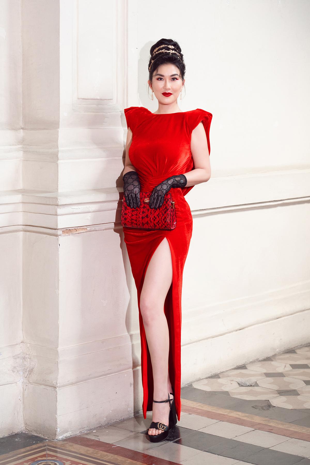 Nữ doanh nhân kết hợp váy nhung đỏ độn vai và găng tay Gucci mang kiểu dáng cổ điển cùng lối trang điểm nổi bật với màu son đỏ tươi, bới tóc cao.