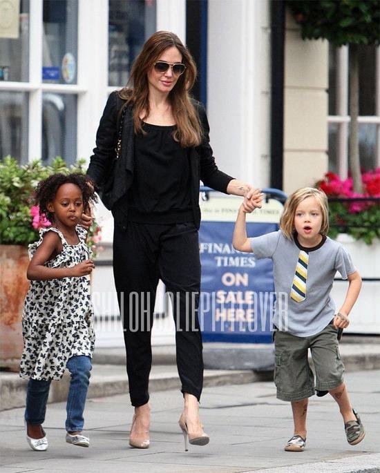 Shiloh (phải) đeo cà vạt, mặc quần áo con trai chơi đùa với chị gái Zahara.