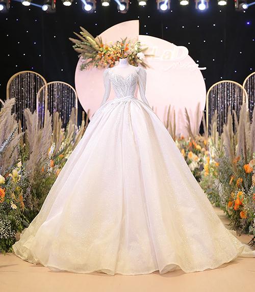 Ở đầu buổi lễ, cô nàng Khánh Linh lựa chọn phần váy xoè bồng rực rỡ với đuôi dài, sử dụng loại vải lưới kim sa cao cấp kết hợp vải chiffon đính Swarovski nhuyễn.