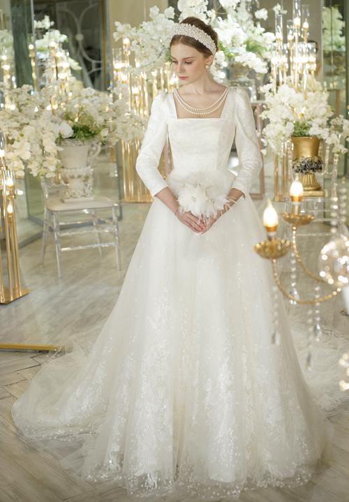 Một thiết kế cổ vuông khác có độ xòe bồng vừa phải để cô dâu dễ dàng di chuyển nếu tổ chức lễ cưới trong không gian nhỏ. Váy bắt sáng tốt nhờ lớp vải đính sequins lấp lánh.