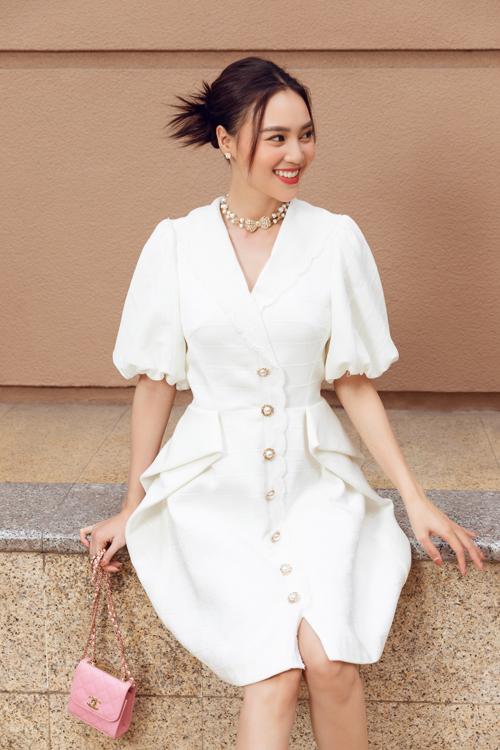 Mặc đầm trắng trang trí hàng cúc điệu đà, Lan Ngọc sử dụng thêm vòng cổ ngọc trai, túi Chanel dáng mini để hoàn thiện set đồ.