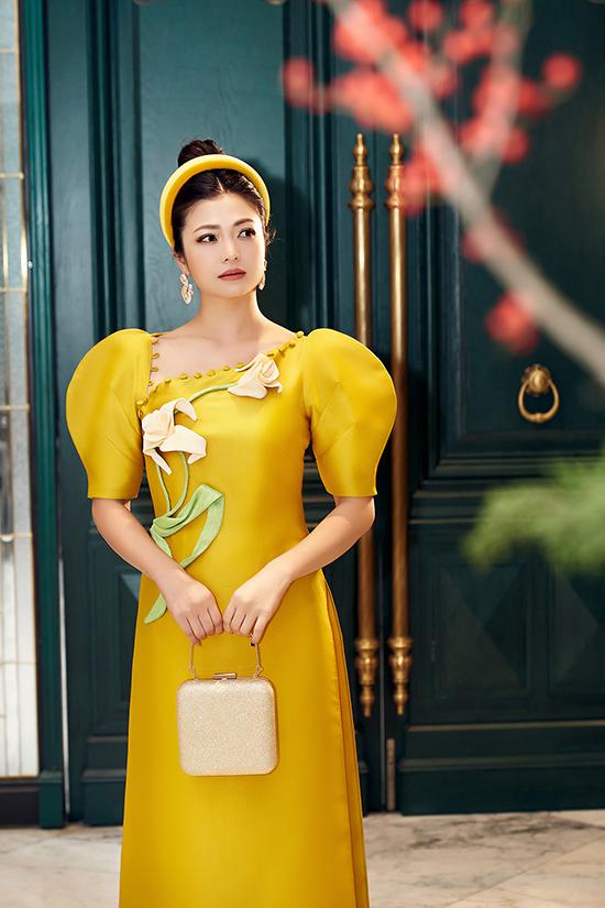 Áo dài trở nên điệu đà hơn với chiếc cổ uốn lượn đính cúc bọc vải cùng chất liệu.