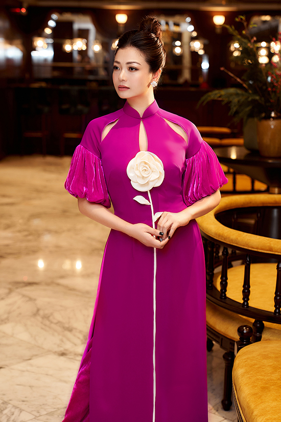 Áo dài nhung cut-out bắt mắt hơn nhờ bông hoa hồng màu trắng trên ngực áo.