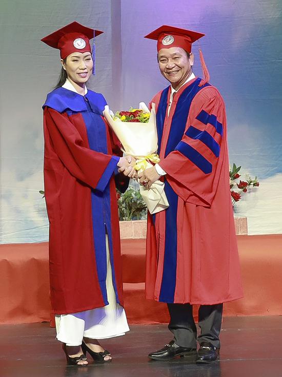 Hiệu trưởng trường Đại học Sân khấu Điện ảnh TP Hồ Chí Minh - PGS -TS Đinh Quang Trung tặng hoa, trao bằng cử nhân cho Trịnh Kim Chi, hôm 11/1.