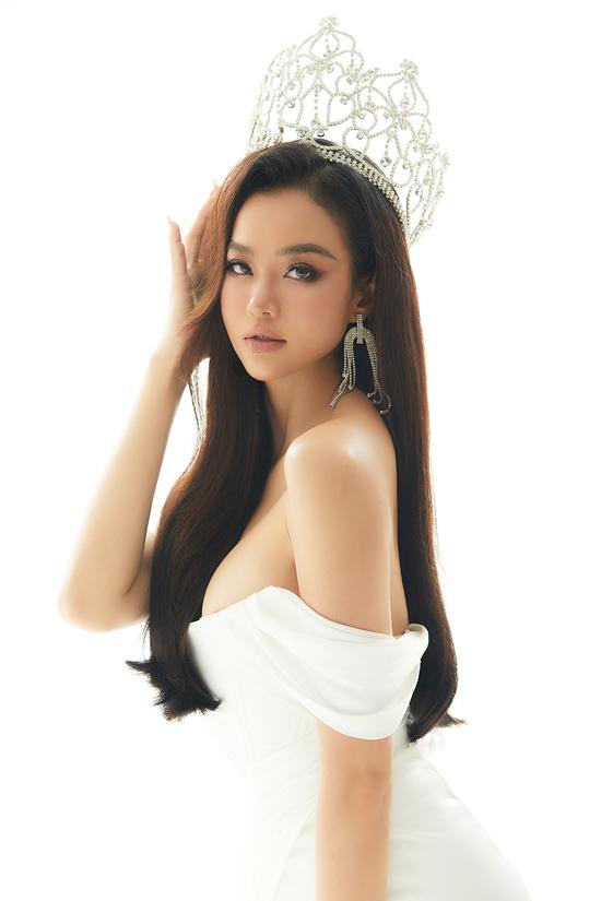 Người đẹp tự tin với vòng một đầy đặn, làn da nâu khỏe khoắn khi mặc váy dạ hội trắng, kiểu trễ vai.