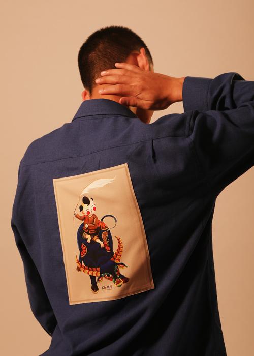 Mẫu áo ngày Tết dành cho phái mạnh được tạo điểm nhấn bởi họa tiết độc quyền. Họa tiết mang mảng mầu dân gian lấy cảm hứng từ hình ảnh vua Đinh Bộ Lĩnh từ thủa ấu thơ, cầm cơ lau cưỡi trâu chơi trận giả.