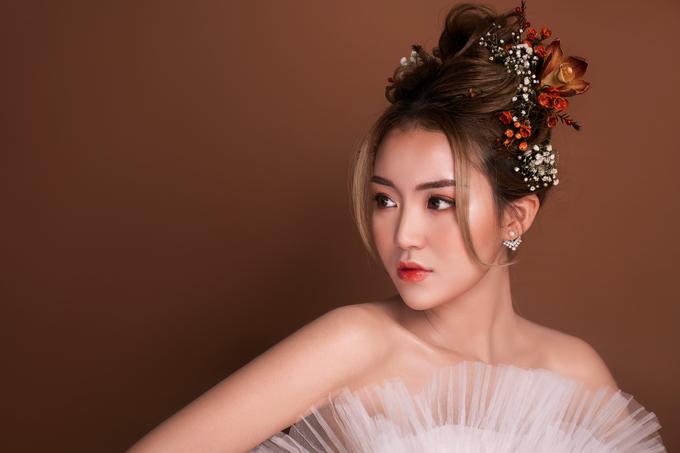 Tiếp tục là layout makeup trong trẻo nhưng được Trang Sun biến tấu với môi màu đỏ cam. Chuyên gia tạo mảng khối rõ ràng, nhấn sáng các vị trí nổi khối như gò má, sống mũi, cằm.