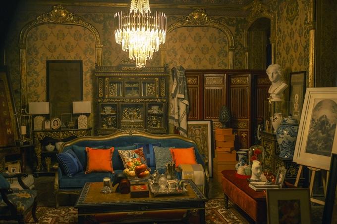Căn phòng được lấp đầy bởi nhiều đồ cổ, tượng, tranh vẽ.