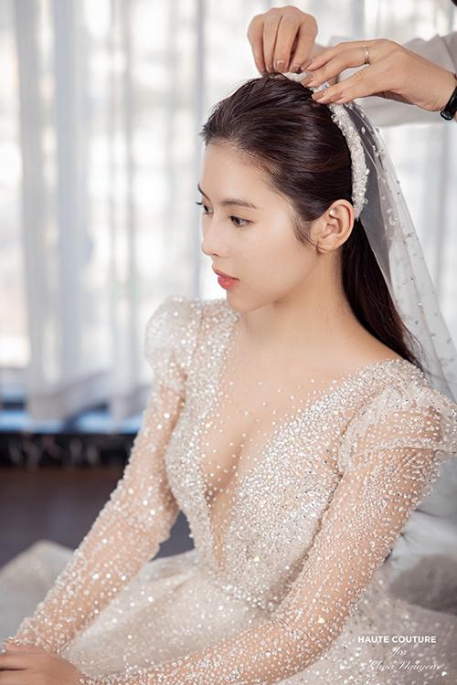 Phụ kiện đi cùng chiếc váy là khăn voan dài cũng được thiết kế riêng và đính pha lê thủ công.