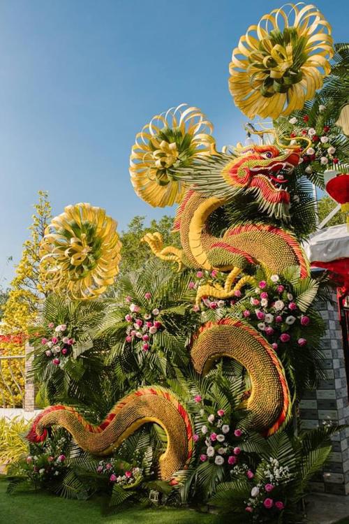 Để làm nên chiếc cổng còn có các nguyên liệu trái cau, lá trầu, ớt đỏ, tỏi, đậu đũa, đậu bắp, lá thơm, hoa hồng và hoa cúc.