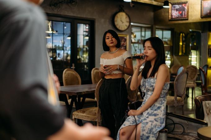 Tuimi mặc áo crop-top còn LyLy cũng khoe vai trần với váy dây. Rapper chăm chú theo dõi phần tập luyện, tổng duyệt chuẩn bị cho đêm nhạc đầu tiên tổ chức tại tụ điểm giải trí do cô và đầu bếp Ngô Thanh Hòa cùng một người bạn thành lập.