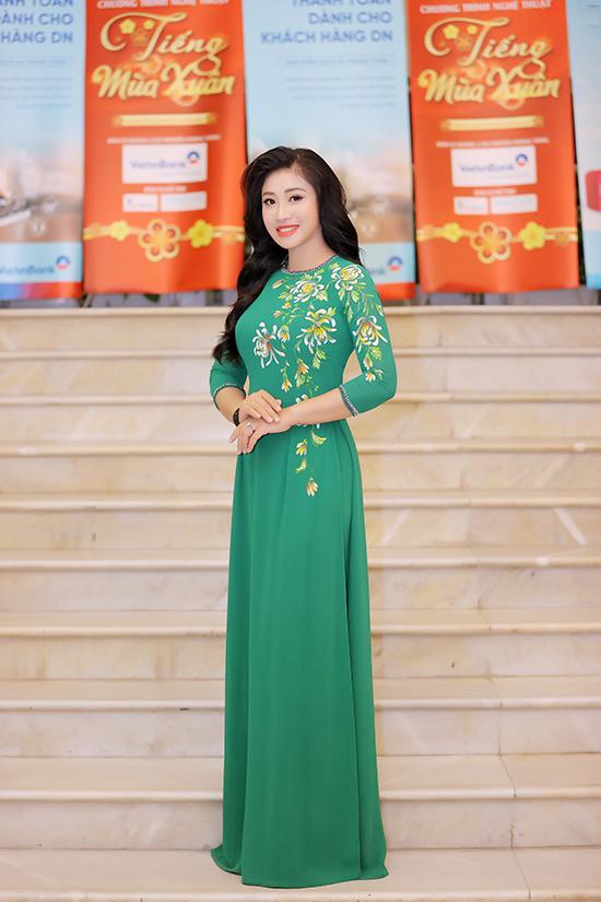Bộ áo dài thứ hai in họa tiết hoa cúc màu rực rỡ trên nền vải xanh lá, hòa nhập với chủ đề mùa xuân của đêm nhạc.