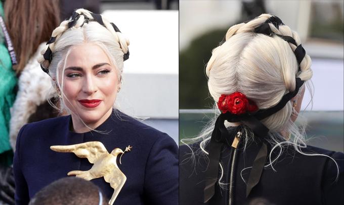 Mái tóc của Lady Gaga  được tết gọn gàng, vấn cao kèm ruy băng tương phản màu tóc, phía sau cài thêm hoa đỏ.