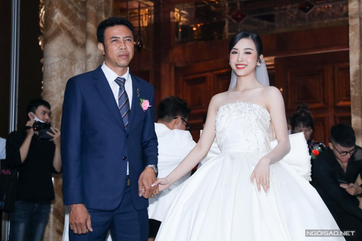 Thuý An khoe vai trần trong chiếc váy cưới thứ hai. Cô được bố nắm chặt tay, chuẩn bị cho phần làm lễ.