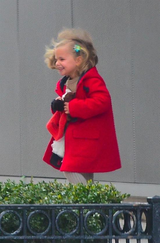 Bé Lea xinh xắn với mái tóc cài nơ hoa, áo khoác đỏ vừa vặn. Cô bé háo hức khi được đi chơi với cả bố và mẹ.