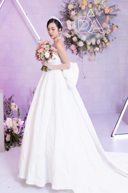 Bộ đôi NTK chia sẻ: Mẫu đầm được sử dụng chất liệu gấm Jacquard với sắc trắng tinh khôi, họa tiết là cánh hoa dập nổi nhằm tôn vẻ sang trọng, quý phái, áp dụng phong cách tối giản.