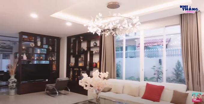 Ở phòng khách là bộ ghế sofa màu trắng, đèn chùm hoa cỏ và một bên tường kính để có thể ngắm vườn xung quanh. Tủ đựng TV cũng là vách ngăn với phòng bếp.