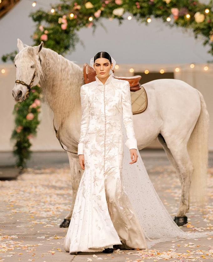 Câu chuyện cổ tích lên đến đỉnh điểm với sự xuất hiện của cô dâu, người bước vào không gian được cưỡi trên một con ngựa trắng. Mặc một chiếc váy dài tay cài cúc phía trước bằng vải crêpe satin có hình tàu hỏa, cô dâu trông như thể đang bước ra từ album cưới những năm 1920.