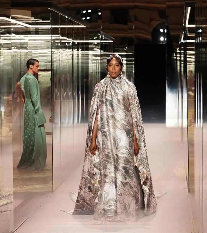 Giữ vị trí vedette, báo đen Naomi Campbell xuất hiện đầy quyền lực với mẫu đầm kèm áo choàng hoa văn cẩm thạch.