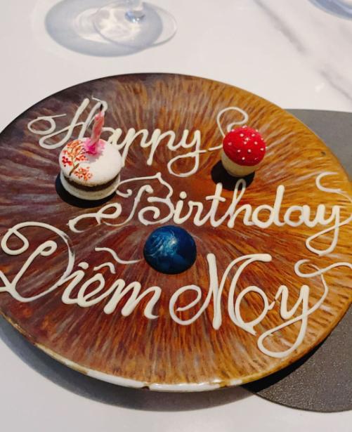 Bánh sinh nhật của Diễm My là 2 chiếc bánh macaron nhỏ xinh, nằm trong set đồ tráng miệng của nhà hàng cùng dòng chữ chúc mừng sinh nhật. Chiếc bánh màu trắng được trang trí cầu kỳ bằng cách vẽ lên những nhánh hoa, chiếc bánh còn lại là hình cây nấm.