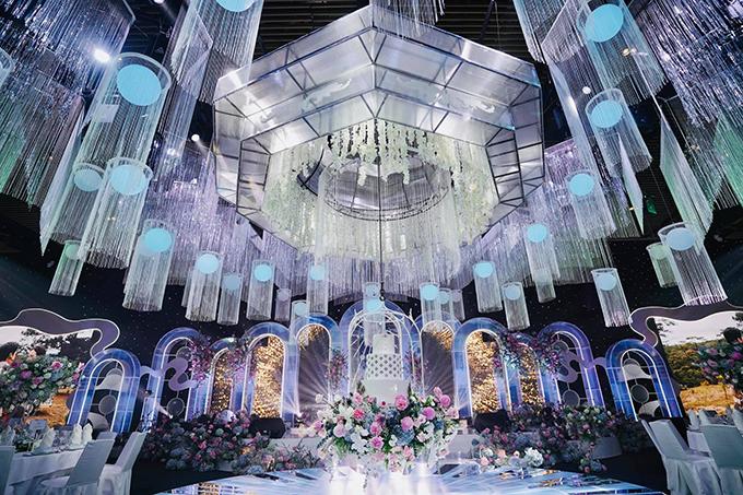 Phía chính giữa đèn thả trần - khu vực trung tâm là bánh cưới treo lơ lửng, được tô điểm với hoa tươi ngoại nhập của uyên ương.