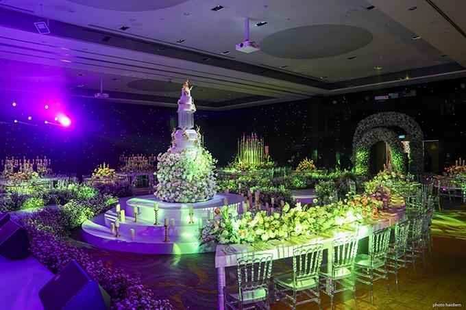 Không gian cưới của uyên ương là một bữa tiệc thị giác với hoa tươi cùng nghệ thuật ánh sáng huyền ảo. Đám cưới của vị đạo diễn tiếp tục gây ấn tượng với bàn tiệc cưới với nhiều hình dạng độc đáo, khác hẳn kiểu bàn tròn thông thường dành cho 10-12 khách. Phần chính giữa sân khấu là bàn bán nguyệt dài được bo tròn ôm trọn vòng cung của chiếc bánh cưới với ghế được xếp đối diện nhau.
