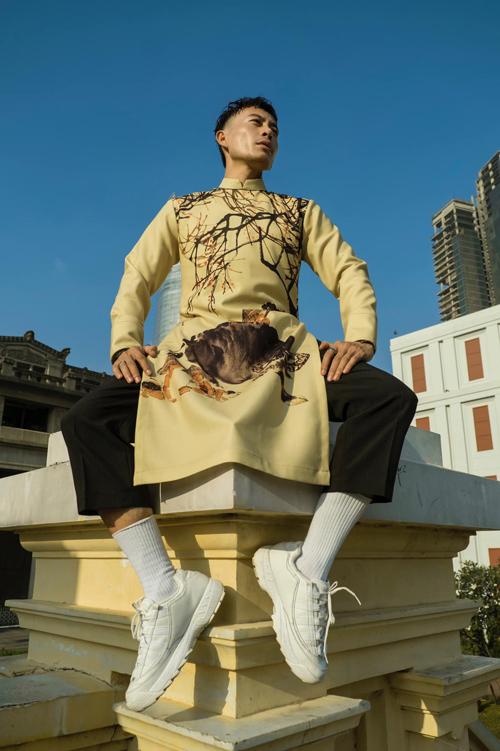 Áo dài cho nam giới trở nên bắt mắt hơn với bức tranh sinh động về quê hương Việt Nam. Nét thanh bình và dung dị được mô tả một cách chân thực qua những hình ảnh thân thuộc như rặng tre, trâu tắm nước, em bé nô đùa.