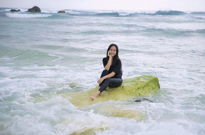 Bella Vũ thích thú tạo dáng chụp ảnh trên một tảng đá và nghe sóng vỗ rì rào quanh mình.