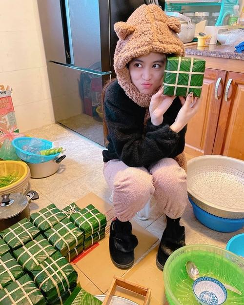Về Bắc đón năm mới cùng gia đình, ca sĩ Hoàng Thùy Linh mặc áo lông, đội mũ lông và mang dép lông giữ ấm, khoe thành quả bánh chưng do cô tự tay gói cùng người thân.