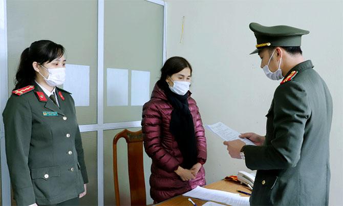 Nghi can Hà (giữa) nghe cảnh sát đọc lệnh bắt. Ảnh: Công an cung cấp