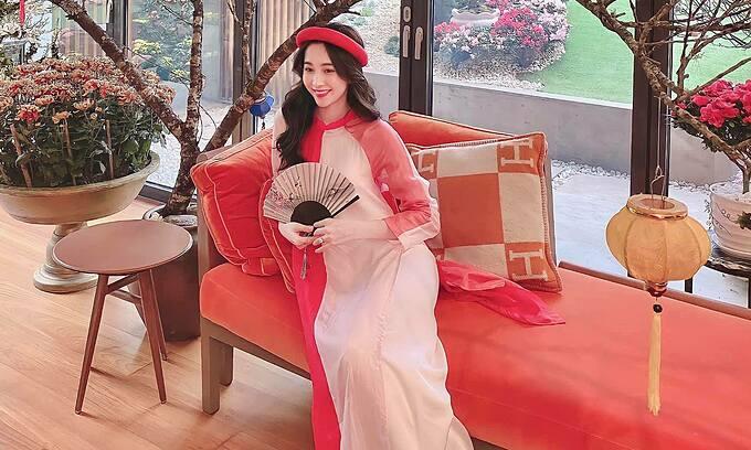Hoa hậu Đặng Thu Thảo diện áo dài, pose hình khoe khuôn viên trang trí Tết của gia đình. Bà mẹ hai con viết: Xuân về cánh én lượn bay.  Trăm hoa đua nở ngất ngây lòng người.