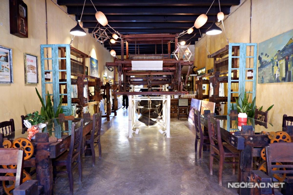 Không gian bên trong quán khá rộng. Một máy dệt lụa cỡ lớn đặt giữa nhà, bàn ghế kiểu cổ bày trí xung quanh, tường treo tranh cho khách vừa nhâm nhi cà phê, vừa ngắm.