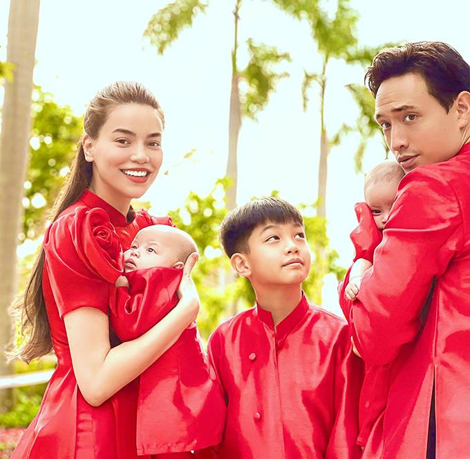 Cả gia đình nữ ca sĩ mặc áo dài cùng chất liệu màu đỏ rực tạo dáng bên vườn nhà. Đây là cái Tết đầu tiên vợ chồng Hồ Ngọc Hà - Kim Lý đón cặp song sinh Lisa và Leon.