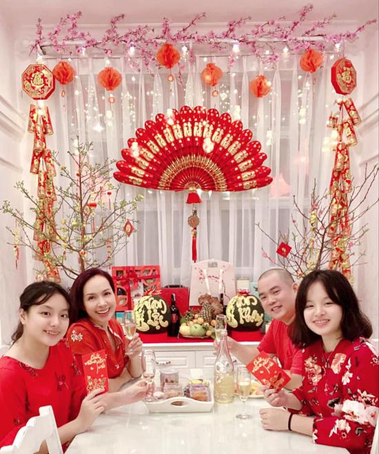 Vợ chồng nhạc sĩ Minh Khang - cựu người mẫu Thuý Hạnh quây quần bên hai cô con gái trong căn biệt thự trang trí đầy đào, mai.