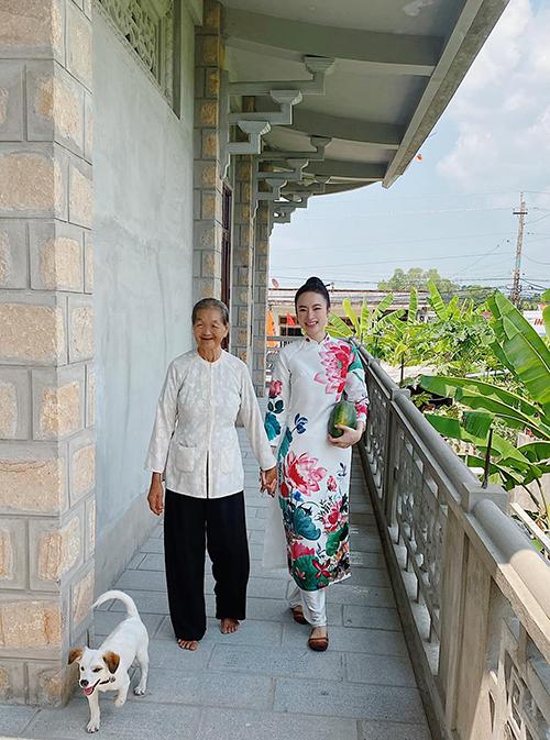 Áo dài trắng tô điểm hoa sen rực rỡ được Angela Phương Trinh sử dụng khi đi thăm nhà thờ tổ được gia đình nội xây ở Long An.