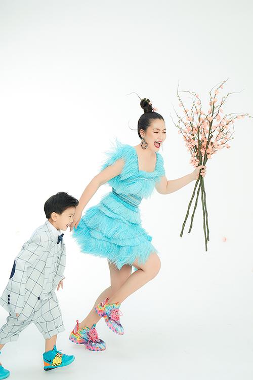 Ngọc Lan diện váy lông vũ tông màu rực rỡ khi tạo dáng năng động cùng bé Louis trong bộ suit đáng yêu.