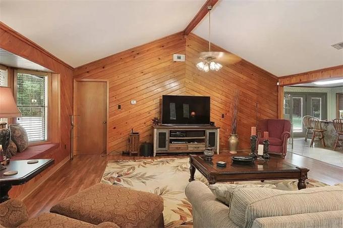 Ngôi nhà một tầng có diện tích xây dựng hơn 200 m2. Tường ốp gỗ và quạt trần phong cách thập niên 1970.