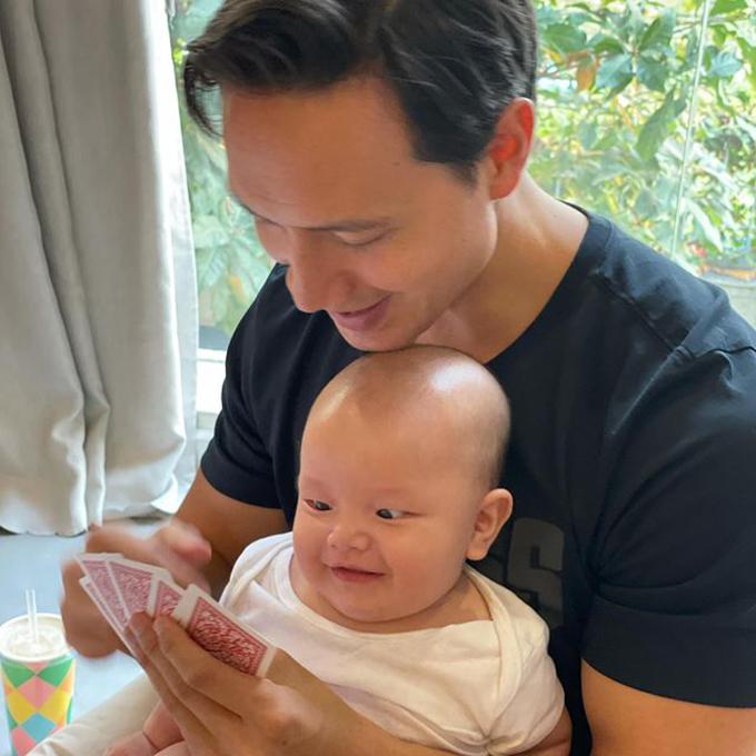 Trong lúc chơi với khách khứa đến chúc Tết, ba Kim Lý vẫn không quên nhiệm vụ trông con. Bé Leon mắt sáng rực, biểu cảm tếu táo trong lòng ba Kim Lý.