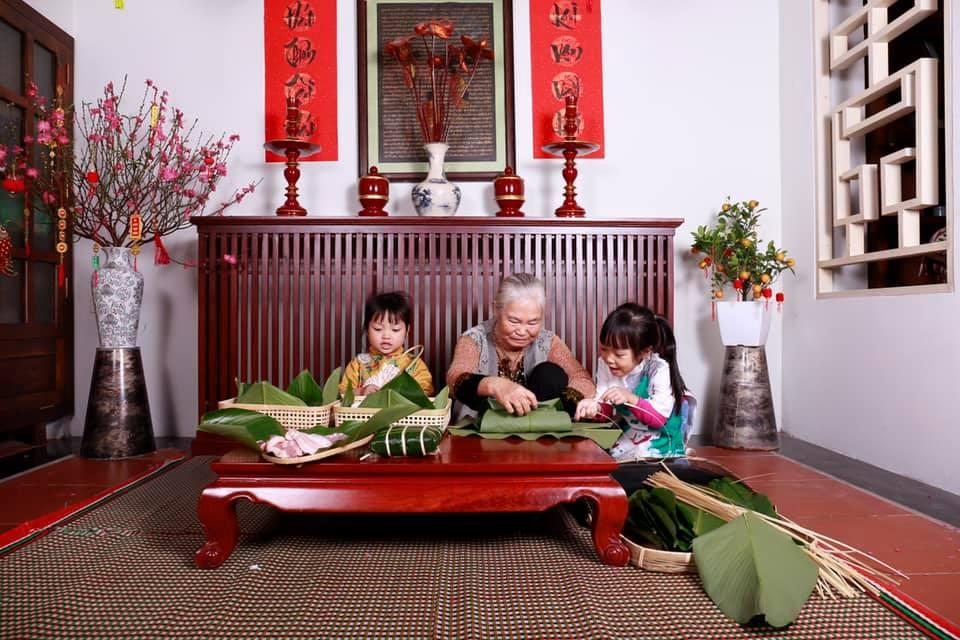 Hai bé gái được bà hướng dẫn gói bánh chưng trong không gian đoàn viên, ấm cúng, bênh cạnh cành đào, cành quất và đôi câu đối Tết.