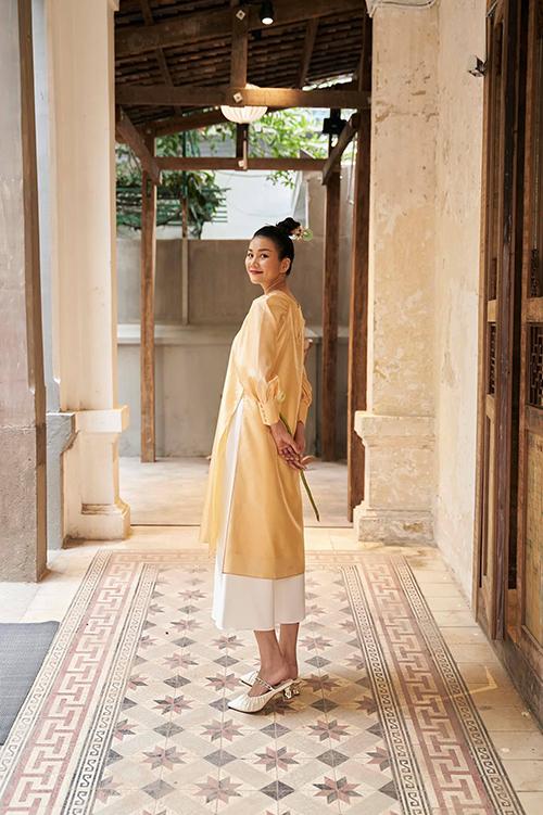 Áo dài cách tân trên tông vàng dịu mắt được kết hợp cùng quần ống lửng sắc màu trang nhã.