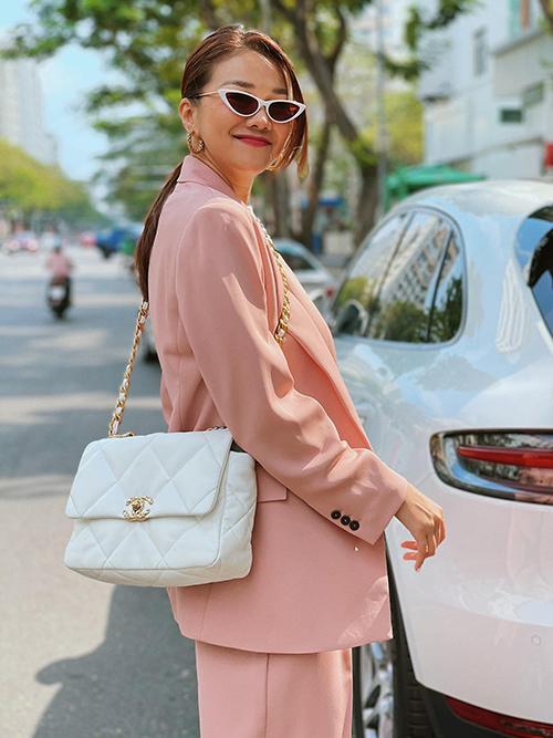 Hai gam màu thanh lịch là hồng phấn và trắng được Thanh Hằng phối hợp ăn ý trên outfit gồm suit, túi Chanel, giày thể thao tiệp màu kính mắt mèo.