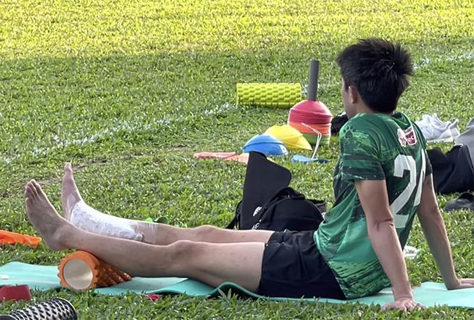 Lee Nguyễn phải chườm đá ở cổ chân, ngồi xem đồng đội tập.