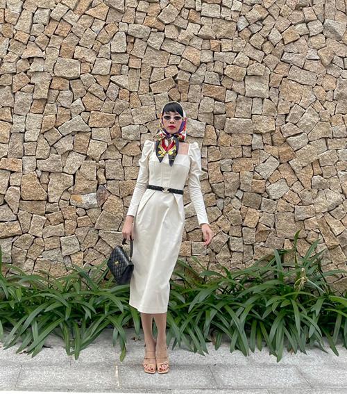 Diện váy liền thân với kiểu tay bồng mang hơi hướng cổ điển, ca sĩ sử dụng túi và dây lưng Chanel để mix đồ hài hoà.