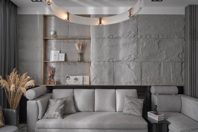 Phong cách thiết kế chủ đạo của biệt thự là hiện đại, sang trọng với tông màu ghi, xám và gỗ nâu. Sự thú vị của không gian sống được thể hiện qua cách phối hợp các vật liệu trong cùng tone màu như vách đá thô sần, bộ sofa da bò mài, ghế bành da bóng kết hợp vải houndstooth hay mặt ốp tường sau sofa, bàn cafe sơn bóng... Ngoài ra sự mở rộng, bố trí các cửa lớn để nguồn sáng tự nhiên đi vào từng không gian, cũng như đèn hắt trang trí tạo thêm điểm nhấn vào buổi tối.